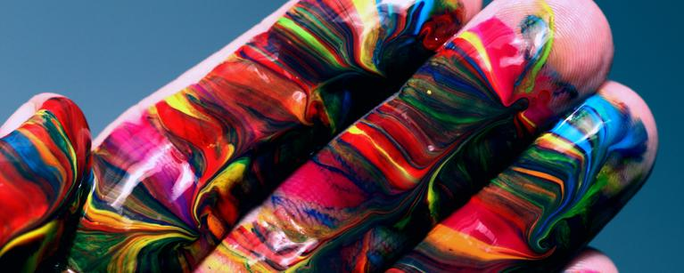 A hand swirled with many different colours of paint