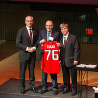 Left to right: President Ed McCauley, Professor Emeritus Al Lucas, UCalgary Law Dean Ian Holloway. Al holds a Calgary Stampeders football jersey with the number 76 on the back.